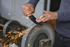 Man hands sharpening the knife. Knife sharpening with sparks flying out stock image