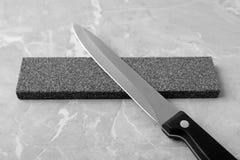 Knife and sharpening stone. On grey background royalty free stock photo