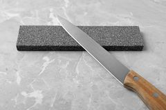 Knife and sharpening stone. On grey background stock photography