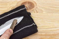 The knife during sharpening on the whetstone. Knife in hand sharpening on a whetstone Stock Photography