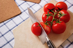 Tomatoes on the board. Knife and sliced tomato on the board stock photo