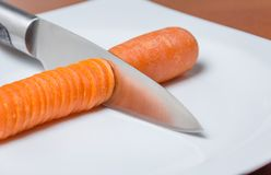 Knife slicing carrot in a white plate over table Royalty Free Stock Photo