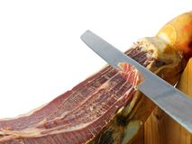Knife slicing jamon or parma ham isolated Royalty Free Stock Photo