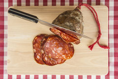 Knife slicing a Spanish sausage called morcon Stock Images