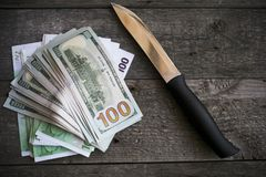 A knife and some fanned out cash laying Stock Image
