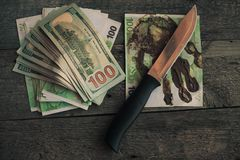 A knife and some fanned out cash laying on wood background . Stock Photos