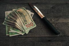 A knife and some fanned out cash laying on wood background . This works for all sorts of illegal activities such as prostitution, Royalty Free Stock Photos