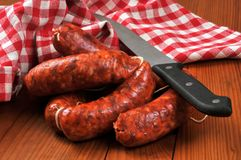 Chorizo to cook with a knife. Knife with spicy sausages on a wooden table stock photography