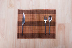 Knife, spoon and fork with napkin on wooden table. Royalty Free Stock Images