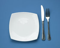 Knife, square plate and fork on blue top view Royalty Free Stock Photography