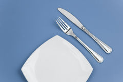 Knife, square plate and fork on blue top view Stock Photos