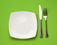 Knife, square white plate, fork on green top view Stock Photos