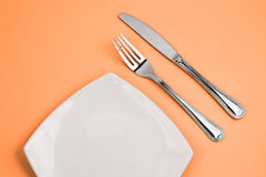 Knife, square white plate, fork on pink top view Royalty Free Stock Images