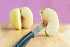 Knife stabbed into chinese pear piece on the wooden board Stock Image