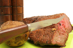 Knife steak & baked potato Stock Images