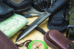Knife surrounded by tourist equipment Stock Photos
