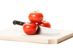 Knife between three tomatoes on wooden board Stock Photography