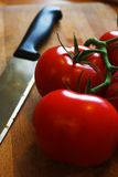 Knife and tomato. On wooden board Royalty Free Stock Photo