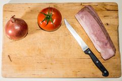 A knife a tomato an onion and some bacon slices in a wooden tray. A tray with some ingredients for cooking Royalty Free Stock Photo