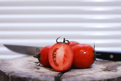A knife and tomatoeson a wooden chopping board Royalty Free Stock Photos