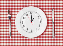 Knife, white plate with clock face and fork on red picnic table. Cloth Royalty Free Stock Images