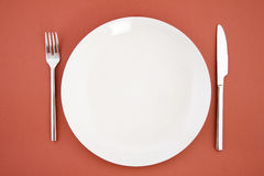 Knife, white plate and fork Stock Photos