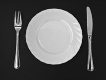 Knife, white plate and fork on black top view Royalty Free Stock Image