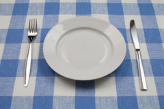 Knife, white plate and fork on blue tablecloth Stock Photography