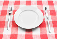 Knife, white plate and fork on checked tablecloth Royalty Free Stock Images