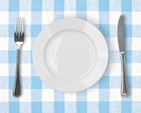 Knife, white plate and fork on checked tablecloth Royalty Free Stock Photography