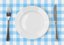 Knife, white plate and fork on checked top view Stock Images