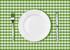 Knife, white plate and fork on green picnic table cloth. Knife, white plate and fork on green picnic tablecloth Stock Photos