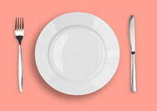Knife, white plate and fork on pink background. Knife, white plate and fork on pink rose background stock photo