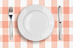 Knife, white plate and fork on pink tablecloth. Knife, white plate and fork on pink checked tablecloth Stock Photography