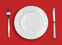 Knife, white plate and fork on red background Stock Image