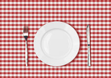 Knife, white plate and fork on red picnic table cloth Stock Images
