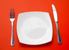 Knife, white plate and fork on red top view Stock Photos