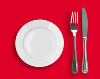 Knife, white plate and fork on red top view Royalty Free Stock Image