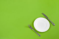 Knife, white round plate, fork on green top view Stock Photo