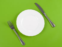 Knife, white round plate, fork on green top view Stock Photos