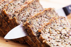 Knife in wholemeal, wholewheat bread on wooden table. Organic, healthy food Stock Photos