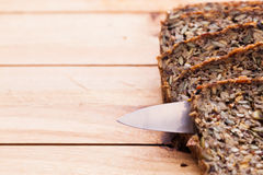 Knife in wholemeal, wholewheat bread on wooden table. Organic, healthy food Royalty Free Stock Image