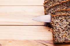 Knife in wholemeal, wholewheat bread on wooden table. Organic, healthy food Stock Image