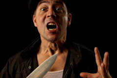 Knife wielding mugger. A crazed  angry knife wielding maniac  criminal mugger  on a black background Royalty Free Stock Photo