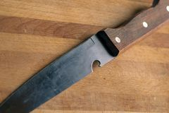 Knife with a wooden handle on a rustic kitchen cutting board stock images