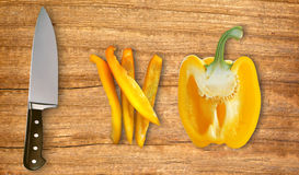 Knife and yellow paprika pepper on cutting board  Royalty Free Stock Images