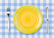 Knife, yellow plate and fork on checked top view Royalty Free Stock Photos