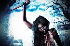 Knife zombi. Bloodthirsty zombi standing at the night cemetery in the mist and moonlight Royalty Free Stock Photography