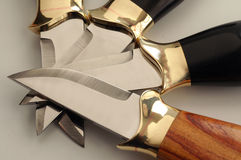 Knifes. 4 hand made knife crossed over each other Royalty Free Stock Photos