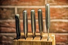 Knifes w drewnianym bloku z ściana z cegieł na tle Obraz Stock
